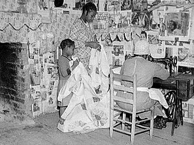 In this 1937 image by Farm Security Administration photographer Arthur Rothstein, Gee's Bend quilter Jorena Pettway sews a quilt as two young girls hold the fabric for her. Courtesy of Library of Congress, photograph by Arthur Rothstein.