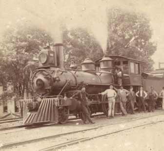 Group standing in front train, probably part of the Southern Railway